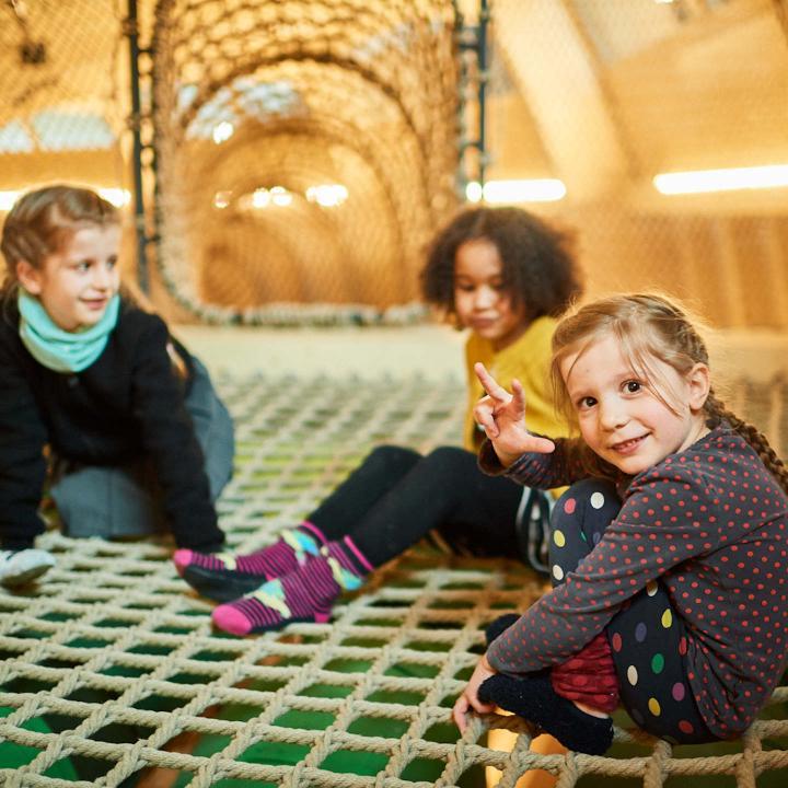 Three children sitting on a net